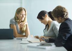 Three adults sitting at table, looking over document Stock Photos