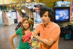 Teenage couple playing game in video arcade - stock photo