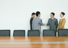 Business executives shaking hands in conference room - stock photo