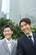 Two young businessmen, laughing, office building in background Stock Photos