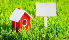 Red house and signboard on grass - stock photo