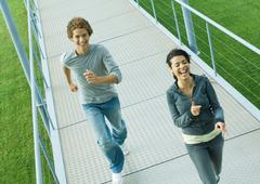 Teenage couple running on walkway, laughing, high angle view - stock photo