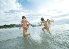 Children running in surf, rear view - stock photo