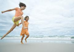Two girls running and jumping on beach Stock Photos