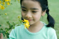 Girl smelling flower, close-up - stock photo