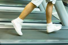 Man running on treadmill, knee down, blurred motion - stock photo