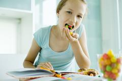 Girl eating junk food while doing homework Stock Photos