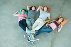 Teenage friends lying on floor with legs joined at ankles - stock photo