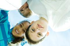 Stock Photo of Children smiling at camera, view from directly below