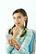 Preteen girl putting on lipstick, looking at camera Stock Photos