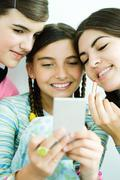 Three young female friends looking at selves in hand mirror, one holding - stock photo
