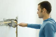 Man filling in hole around plumbing in wall with grout Stock Photos