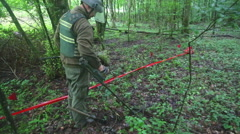 Man trying to detect mine in demining process in the middle of forest. Stock Footage