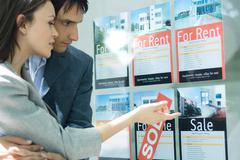 Couple looking at properties in window of real estate agency Stock Photos