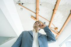 Man in suit using cell phone, bare pipes overhead, low angle view Stock Photos