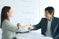 Woman and man shaking hands across table in architect firm Stock Photos