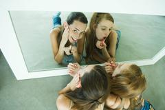 Stock Photo of Two friends lying on ground, applying lipstick, looking in mirror, one looking