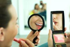 Two young friends applying lipstick, looking at selves in hand mirrors, cropped - stock photo