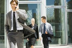Male and female business colleagues talking as they leave office building, man Stock Photos