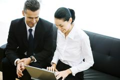 Male and female business associates sitting in lobby, using laptop, smiling - stock photo