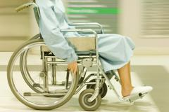 Cropped view of man using wheelchair, dressed in hospital gown, blurred motion - stock photo