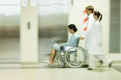 Hospital staff pushing man in wheelchair, blurred motion - stock photo