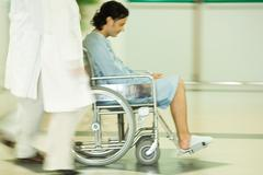 Medical staff pushing man in wheelchair, blurred motion - stock photo