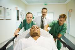 Emergency room staff pushing man on stretcher Stock Photos