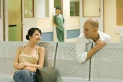Two adults sitting in hospital waiting room, chatting Kuvituskuvat