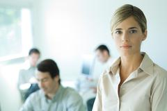 Young businesswoman looking at camera, head and shoulders, associates in Stock Photos
