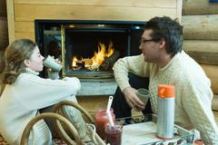 Young man and teenage girl sitting by fireplace, drinking hot beverages, looking Kuvituskuvat