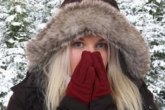 Young woman freezing in the cold in winter in the woods Stock Photos