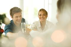 Couple making a toast with champagne, smiling, selective focus - stock photo
