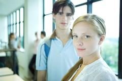 Female student smiling at camera, sideways glance, male peer in background Stock Photos