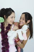 Two young female friends with stuffed animals, smiling at each other, portrait - stock photo