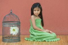 Girl in sundress kneeling on floor, looking at camera, next to birdcage - stock photo