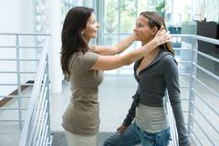 Mother and teenage girl together, woman pushing daughter's hair back, side view - stock photo