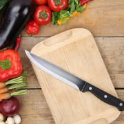 healthy eating preparing and slicing vegetables knife on cutting board - stock photo