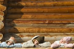 Three preteen or teen girls standing on deck of log cabin, resting heads on Stock Photos