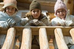 Three preteen or teen girls standing on deck of log cabin, looking down at - stock photo