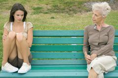Teenage girl sitting apart from grandmother on bench, arms folded, looking down - stock photo