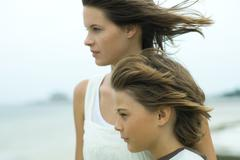 Two siblings looking away together, both being blown by breeze Stock Photos