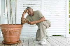 Man kneeling beside potted plant, looking down at dead leaves - stock photo
