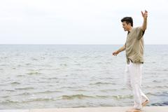 Man walking barefoot with arms out along water's edge Stock Photos