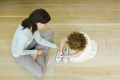 Mother and little girl sitting on floor, girl learning to tie shoe laces, view Stock Photos