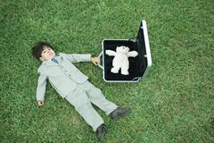 Little boy in full suit, lying on grass, next to open briefcase containing teddy - stock photo