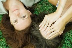Mother and teen daughter lying on the ground together, girl covering face with Stock Photos