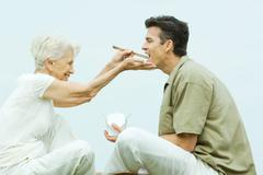 Senior woman feeding adult son takeout food with chopsticks, side view Stock Photos