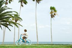 Boy riding bicycle beside palm trees, side view Stock Photos