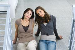 Mother and daughter sitting on the ground together, both looking up at camera Stock Photos